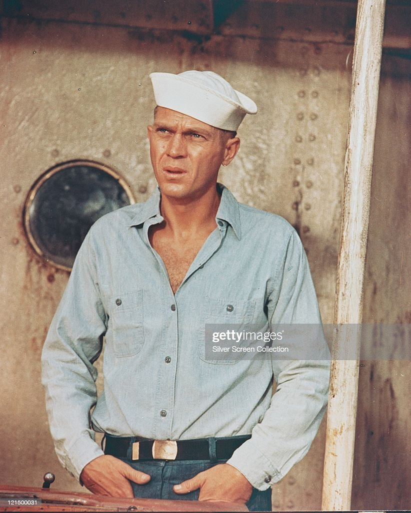 Steve McQueen (1930-1980), US actor, weaing an open-necked blue shirt with a white sailor hat in a publicity still issued for the film, 'The San Pebbles', 1963. The war film, directed by Robert Wise (1914-2005), starred McQueen as 'Jake Holman'.