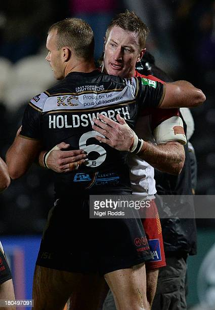 Steve Menzies of Catalan Dragons hugs Daniel Holdsworth of Hull FC after the Super League Play Off between Hull FC and Catalan Dragons at the KC...