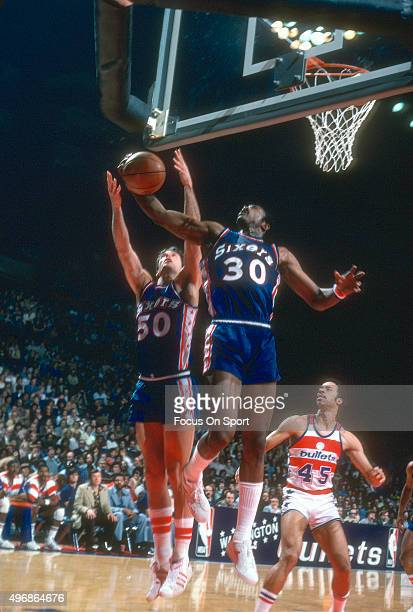 Steve Mix of the Philadelphia 76ers fights for a rebound with teammate George McGinnis against the Washington Bullets during an NBA basketball game...
