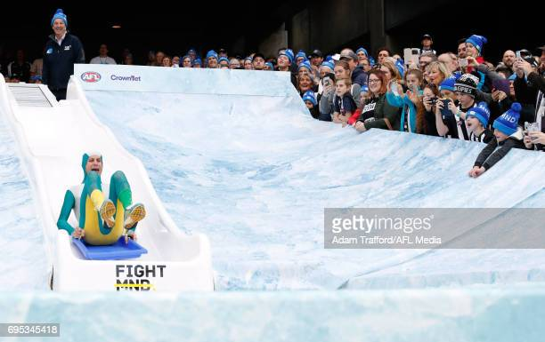 Steve Moneghetti heads down the slide for the Big Freeze MND fundraiser during the 2017 AFL round 12 match between the Melbourne Demons and the...