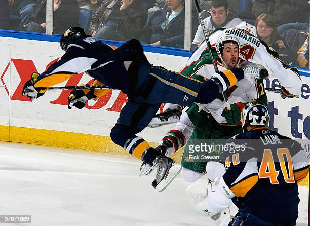 Steve Montador of the Buffalo Sabres gets airborne and strikes Cal Clutterbuck of the Minnesota Wild with his skate as Patrick Lalime of the Sabers...