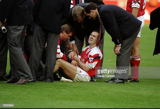 Steve Morrow of Arsenal sits in pain after being dropped by team mate Tony Adams during the celebrations after the Coca Cola Cup final against...
