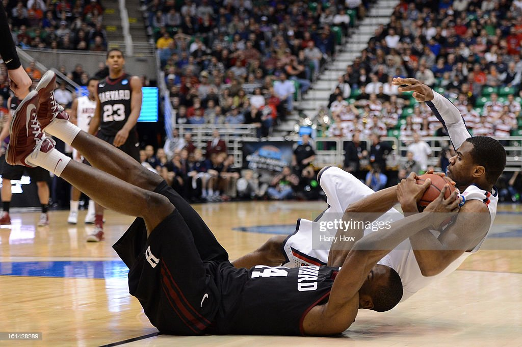 Steve Moundou-Missi #14 of the Harvard Crimson and Kevin Parrom #3 of the Arizona Wildcats battle for a loose ball in the second half during the third round of the 2013 NCAA Men's Basketball Tournament at EnergySolutions Arena on March 23, 2013 in Salt Lake City, Utah.