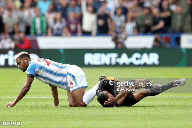 Steve Mounie of Huddersfield Town and Isaac Hayden of Newcastle United reacts after a collision during the Premier League match between Huddersfield...