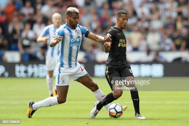 Steve Mounie of Huddersfield Town and Isaac Hayden of Newcastle United battle for possession during the Premier League match between Huddersfield...