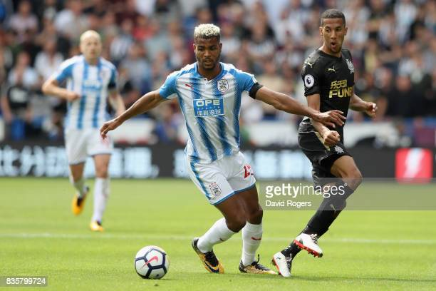 Steve Mounie of Huddersfield Town attempts to get past Isaac Hayden of Newcastle United during the Premier League match between Huddersfield Town and...