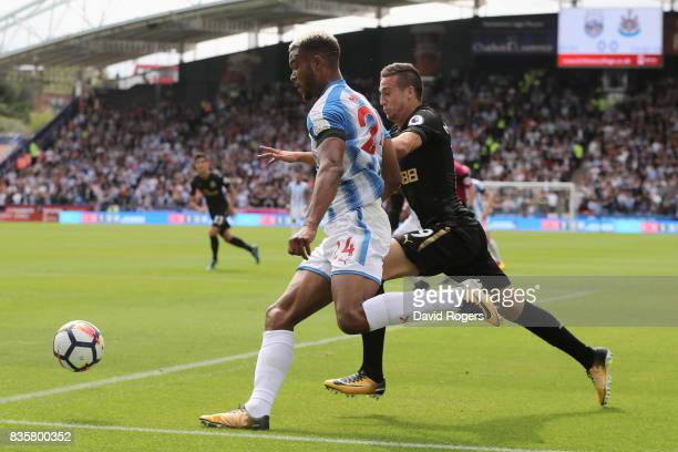 Steve Mounie of Huddersfield Town attempts to get past Javi Manquillo of Newcastle United during the Premier League match between Huddersfield Town...