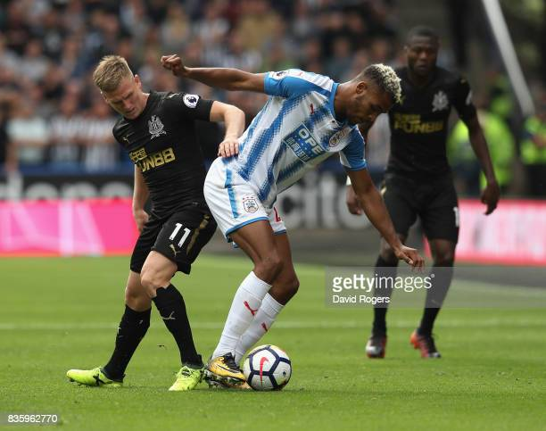 Steve Mounie of Huddersfield Town is challenged Matt Ritchie during the Premier League match between Huddersfield Town and Newcastle United at John...
