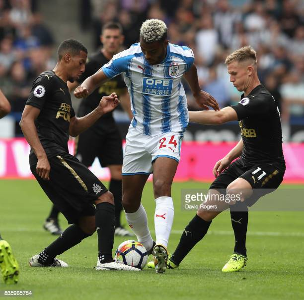 Steve Mounie of Huddersfield Town is tackled during the Premier League match between Huddersfield Town and Newcastle United at John Smith's Stadium...