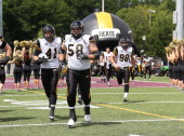Steve Myddelton and Erik Harris of the Hamilton TigerCats run onto field prior to play against the Montreal Alouettes during a preseason CFL football...