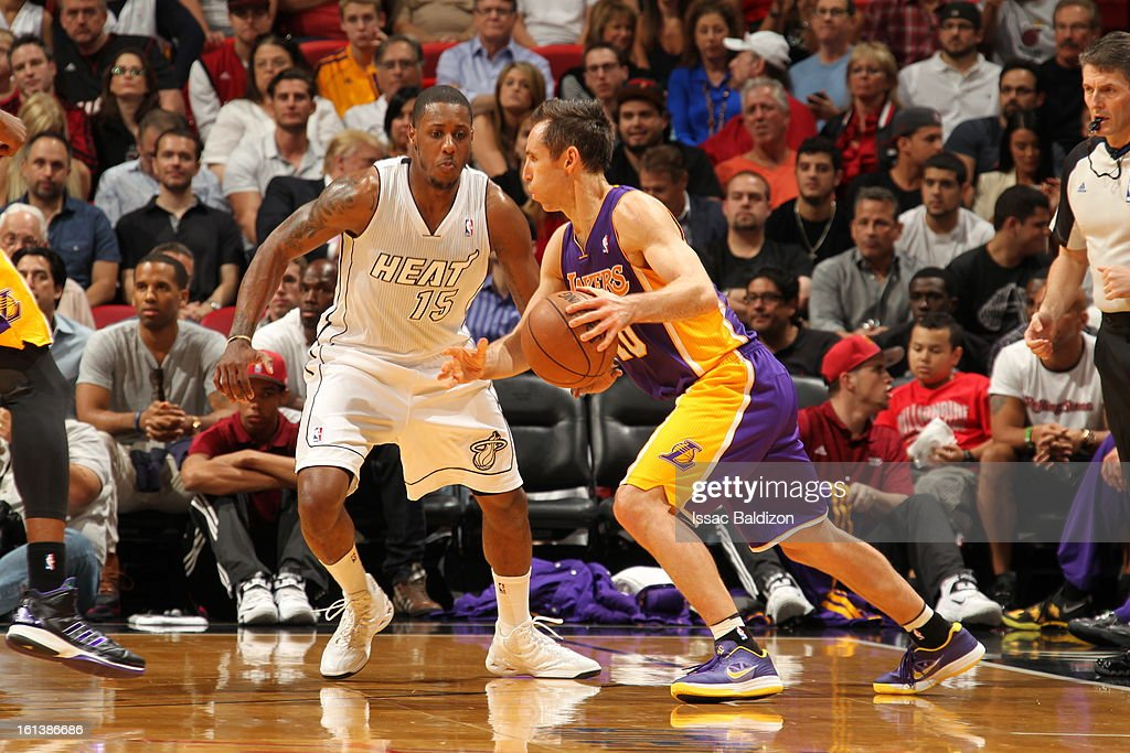 Steve Nash #10 of the Los Angeles Lakers drives against Mario Chalmers #15 of the Miami Heat during a game between the Los Angeles Lakers and the Miami Heat on February 10, 2013 at American Airlines Arena in Miami, Florida.