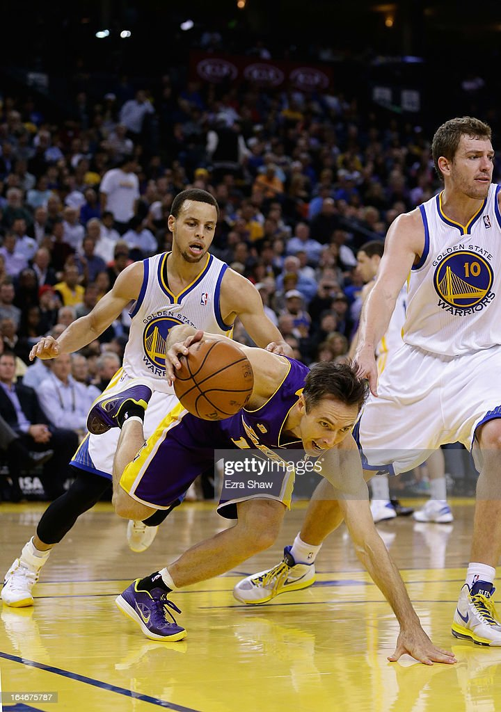 Steve Nash #10 of the Los Angeles Lakers loses his balance as he dribbles past Stephen Curry #30 of the Golden State Warriors at Oracle Arena on March 25, 2013 in Oakland, California.