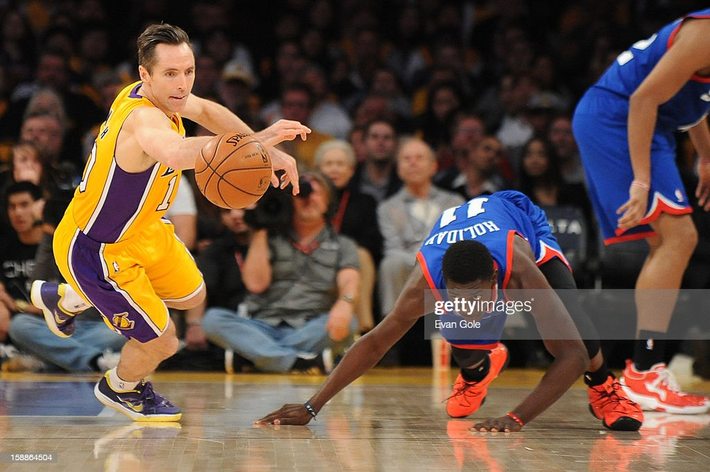 Steve Nash #10 of the Los Angeles Lakers reaches for a loose ball against Jrue Holiday #11 of the Philadelphia 76ers at Staples Center on January 1, 2013 in Los Angeles, California.