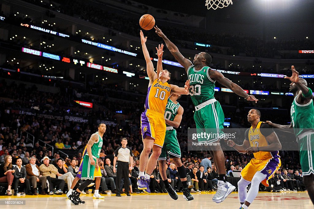 Steve Nash #10 of the Los Angeles Lakers shoots a layup against Brandon Bass #30 and Avery Bradley #0 of the Boston Celtics at Staples Center on February 20, 2013 in Los Angeles, California.