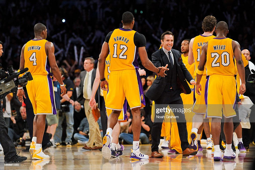 Steve Nash #10 of the Los Angeles Lakers, wearing street clothes, celebrates with teammates Dwight Howard #12 and Jodie Meeks #20 during a timeout in a game against the Houston Rockets at Staples Center on April 17, 2013 in Los Angeles, California.
