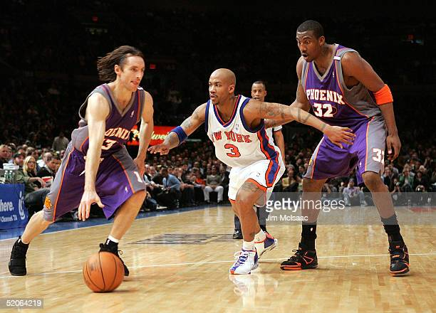 Steve Nash of the Phoenix Suns dribbles in front of teammate Amare Stoudemire and Stephon Marbury of the New York Knicks on January 25 2005 at...