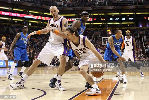 Steve Nash of the Phoenix Suns drives the ball past Marcin Gortat and Brendan Haywood of the Dallas Mavericks during the NBA game at US Airways...