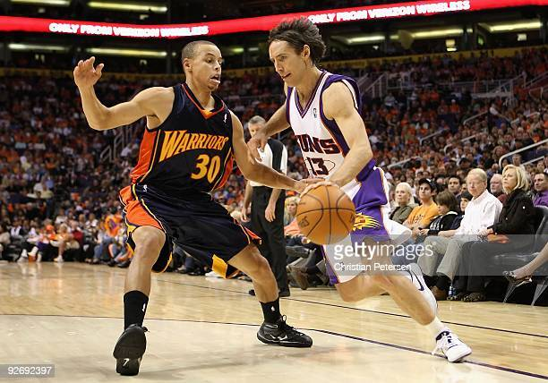 Steve Nash of the Phoenix Suns drives the ball past Stephen Curry of the Golden State Warriors during the NBA game at US Airways Center on October 30...