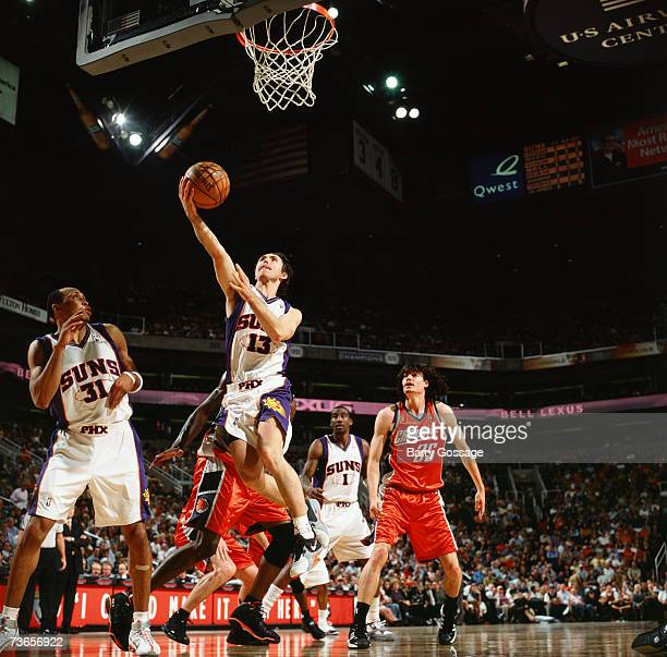 Steve Nash of the Phoenix Suns drives to the basket for a layup past Adam Morrison of the Charlotte Bobcats during a game at US Airways Center on...