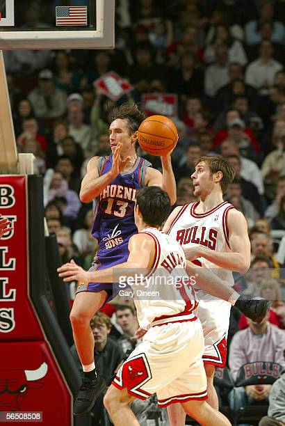 Steve Nash of the Phoenix Suns passes past Kirk Hinrich and Andres Nocioni of the Chicago Bulls during the NBA game on December 31 2005 at the United...