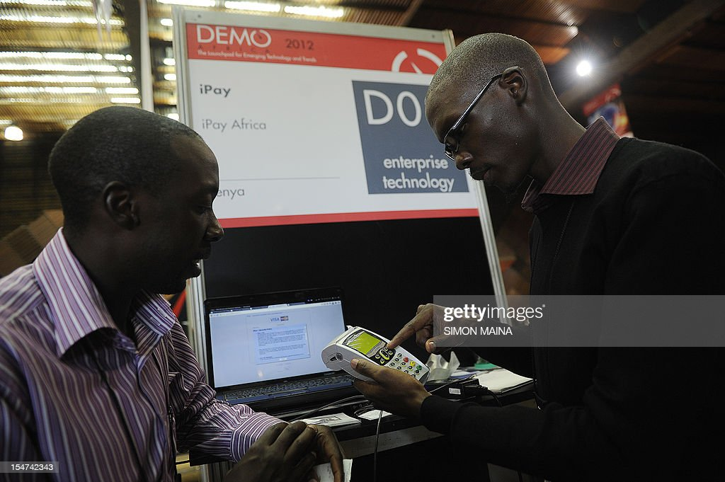 Steve Nyumba (L) listens as entrepreneur Philip Nyamwaya presents an electronic payment system on October 25, 2012, during the DEMO Africa technology fair at the Kenyatta International Conference Center in Nairobi, where some fourty start-up firms in the technology and communication business are seeking to raise $60 million (Sh5.04 billion) by showcasing their products or prototypes. Nairobi over the past decade has earned the nickname 'Silicon Sahara' for its entrepreneurial prowess and growing culture of innovation and research. The DEMO Africa conference takes place from October 24 to 26 and provides a platform for start-ups from across Africa to pitch for growth capital and strategic partnerships, with the aim of developing the companies' ability to compete with tech startups across the globe.