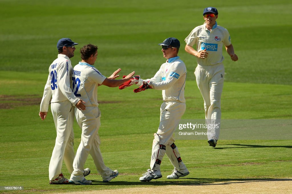 Steve O'Keefe of the Blues (2-L) celebrates with teammates after dismissing Cameron White of the Bushrangers during day three of the Sheffield Shield match between the Victorian Bushrangers and the New South Wales Blues at Melbourne Cricket Ground on March 9, 2013 in Melbourne, Australia.