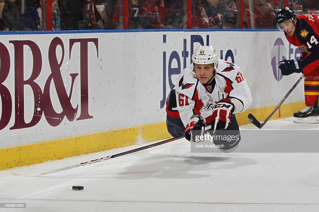 Steve Oleksy #61 of the Washington Capitals attempts to pass the puck while he is off his skates in the third period against the Florida Panthers at the BB&T Center on April 6, 2013 in Sunrise, Florida. The Capitals defeated the Panthers 4-3.