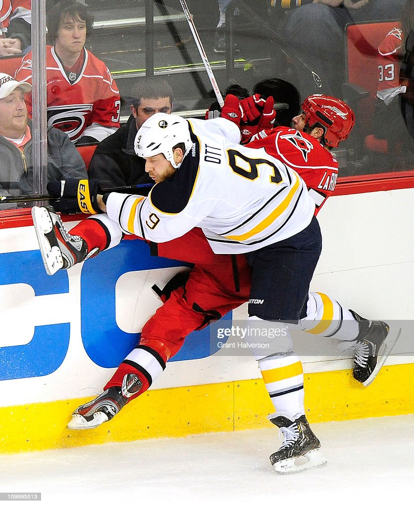 Steve Ott #9 of the Buffalo Sabres checks Chad LaRose #59 of the Carolina Hurricanes during play at PNC Arena on January 24, 2013 in Raleigh, North Carolina. Carolina defeated Buffalo, 6-3.
