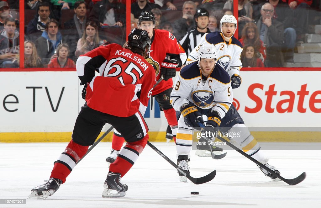 Steve Ott #9 of the Buffalo Sabres defends against a puck-carrying Erik Karlsson #65 of the Ottawa Senators during an NHL game at Canadian Tire Centre on February 6, 2014 in Ottawa, Ontario, Canada.