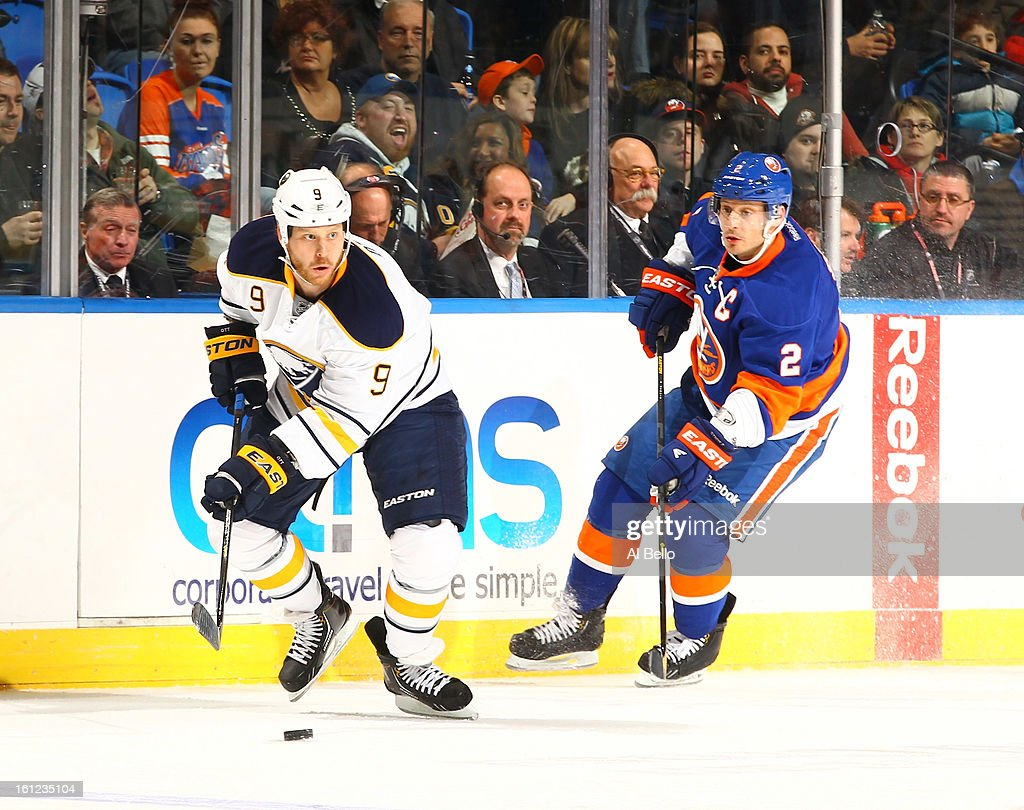 Steve Ott #9 of the Buffalo Sabres handles the puck as Mark Streit #2 of the New York Islanders chases during their game at Nassau Veterans Memorial Coliseum on February 9, 2013 in Uniondale, New York.
