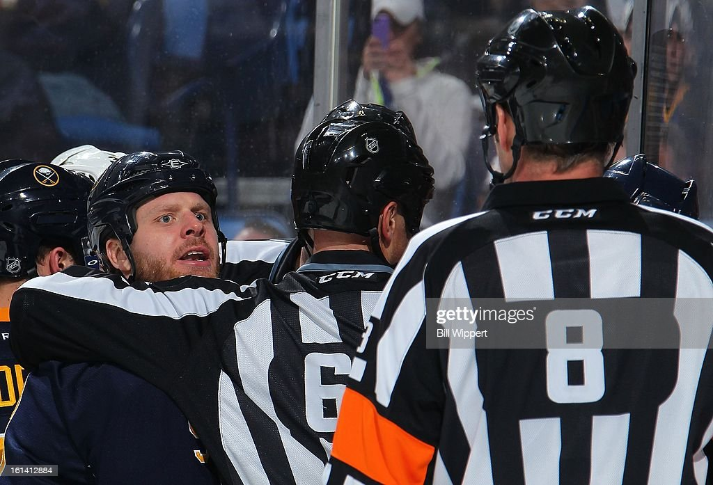 Steve Ott #9 of the Buffalo Sabres has words with linesman Darren Gibbs #66 and referee Dave Jackson #8 during their game against the Boston Bruins on February 10, 2013 at the First Niagara Center in Buffalo, New York.