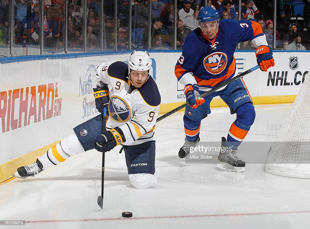 Steve Ott #9 of the Buffalo Sabres protects the puck against Travis Hamonic #3 of the New York Islanders at Nassau Veterans Memorial Coliseum on Febuary 9, 2013 in Uniondale, New York.