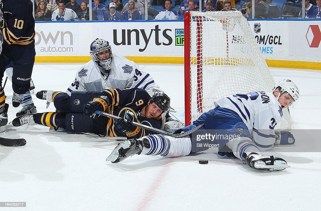 Steve Ott #9 of the Buffalo Sabres reaches for the puck against James Reimer #34 and Cral Gunnarsson #36 of the Toronto Maple Leafs on March 21, 2013 at the First Niagara Center in Buffalo, New York. Buffalo defeated Toronto, 5-4.