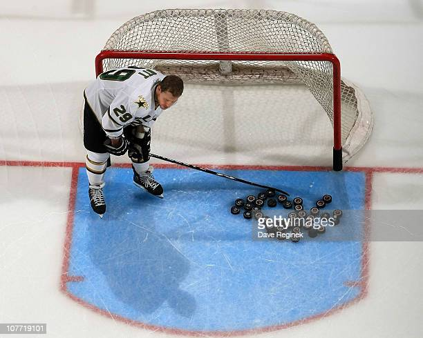 Steve Ott of the Dallas Stars digs the pucks out of the net in warmups before an NHL game against the Detroit Red Wings and the at Joe Louis Arena on...