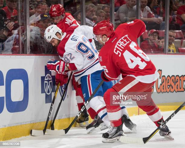 Steve Ott of the Montreal Canadiens battles along the boards for the puck with Drew Miller and Ben Street of the Detroit Red Wings during an NHL game...