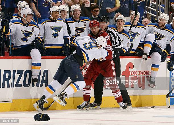 Steve Ott of the St Louis Blues and Kyle Chipchura of the Arizona Coyotes tangle in front of the Blues bench during the third period at Gila River...