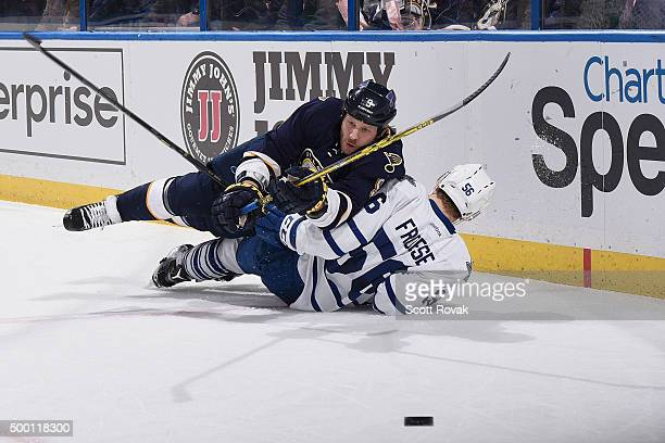 Steve Ott of the St Louis Blues falls over Byron Froese of the Toronto Maple Leafs while chasing down the puck at the Scottrade Center on December 5...