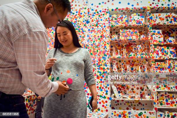 Steve Pak places dots on the 55month pregnant belly of his wife Cindy Pak as the last visitors apply the final dots to the Obliteration Room on the...