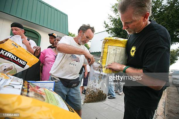 Steve Partain of the Westside Animal Rescue Program and volunteer Dennis Williams prepare bags of dog food during a weekly outreach event on August...
