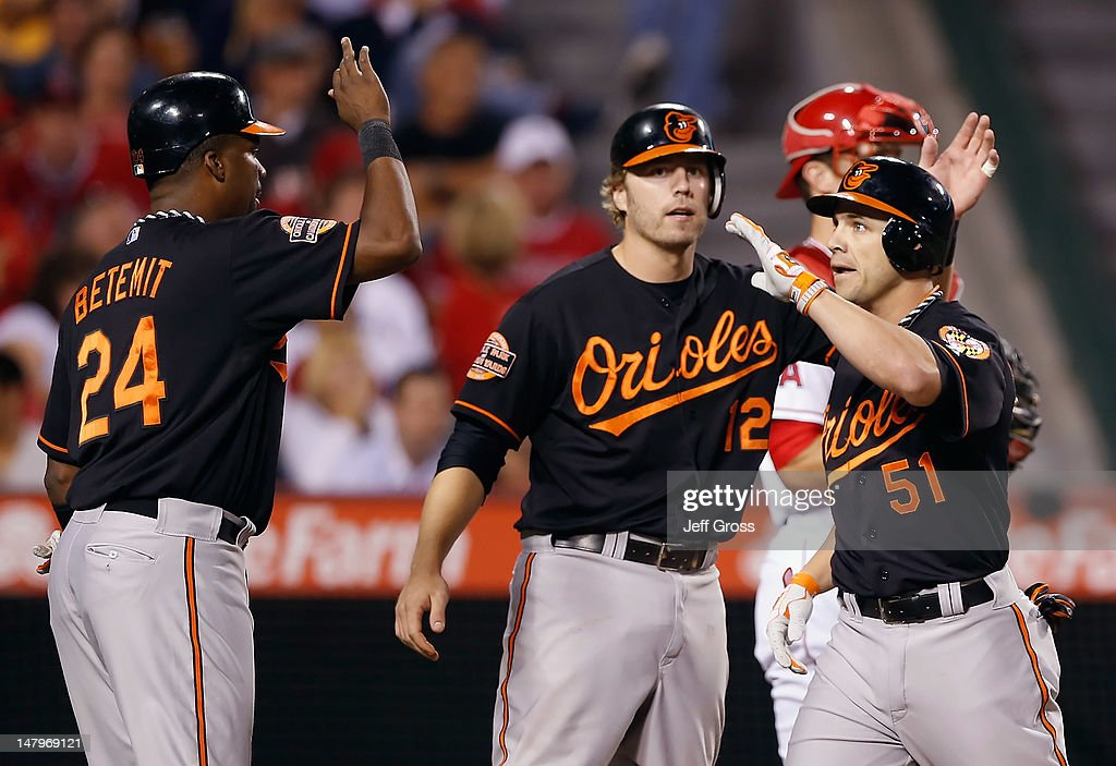 Steve Pearce (R) #51 of the Baltimore Orioles is congratulated by Wilson Betemit (L) #24 and Mark Reynolds #12 after hitting a three-run home run in the fifth inning against the Los Angeles Angels of Anaheim at Angel Stadium of Anaheim on July 6, 2012 in Anaheim, California.