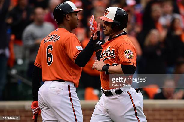 Steve Pearce celebrates with teammate Jonathan Schoop after scoring on a sacrifice fly to center field hit by Caleb Joseph of the Baltimore Orioles...