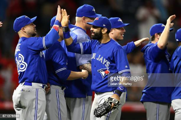 Steve Pearce congratulates Jose Bautista of the Toronto Blue Jays after defeating the Los Angeles Angels of Anaheim 87 in a thirteen inning game at...