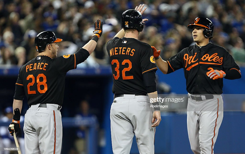 Steve Pearce #28, Matt Wieters #32 and Danny Valencia #35 of the Baltimore Orioles celebrate Valencia's two-run home run against the Toronto Blue Jays during MLB action at the Rogers Centre May 24, 2013 in Toronto, Ontario, Canada.