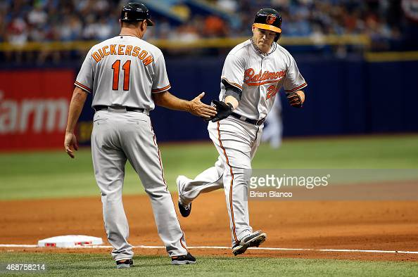 Steve Pearce of the Baltimore Orioles celebrates his home run with third base coach Bobby Dickerson as he rounds the bases during the sixth inning of...