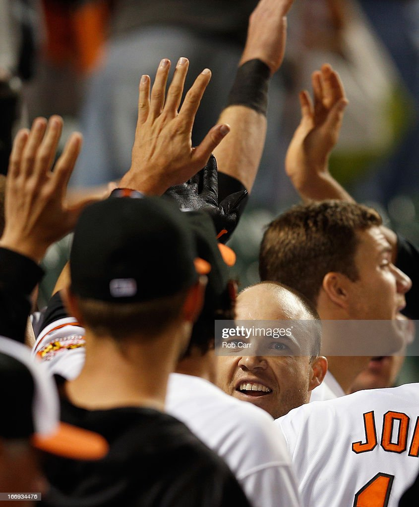 Steve Pearce #28 of the Baltimore Orioles celebrates in the dugout after hitting a two RBI home run against the Tampa Bay Rays in the seventh inning of the Orioles 10-6 extra inning win at Oriole Park at Camden Yards on April 18, 2013 in Baltimore, Maryland.