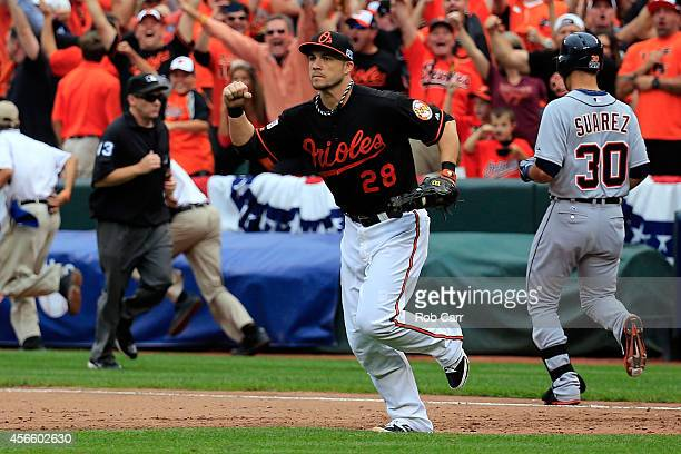 Steve Pearce of the Baltimore Orioles celebrates tagging out Eugenio Suarez of the Detroit Tigers for the last out of the ninth inning to defeat the...