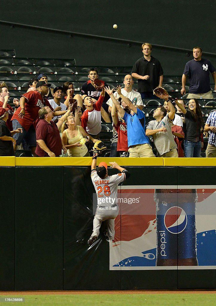 Steve Pearce #28 of the Baltimore Orioles climbs the left field wall in an attempt to catch a home run off the bat of Aaron Hill (not pictured) of the Arizona Diamondbacks at Chase Field on August 12, 2013 in Phoenix, Arizona.