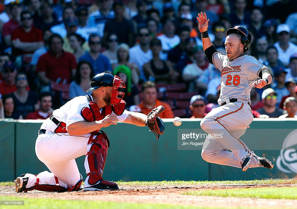 Steve Pearce of the Baltimore Orioles is safe as David Ross of the Boston Red Sox takes a late throw in the seventh inning at Fenway Park on July 6...