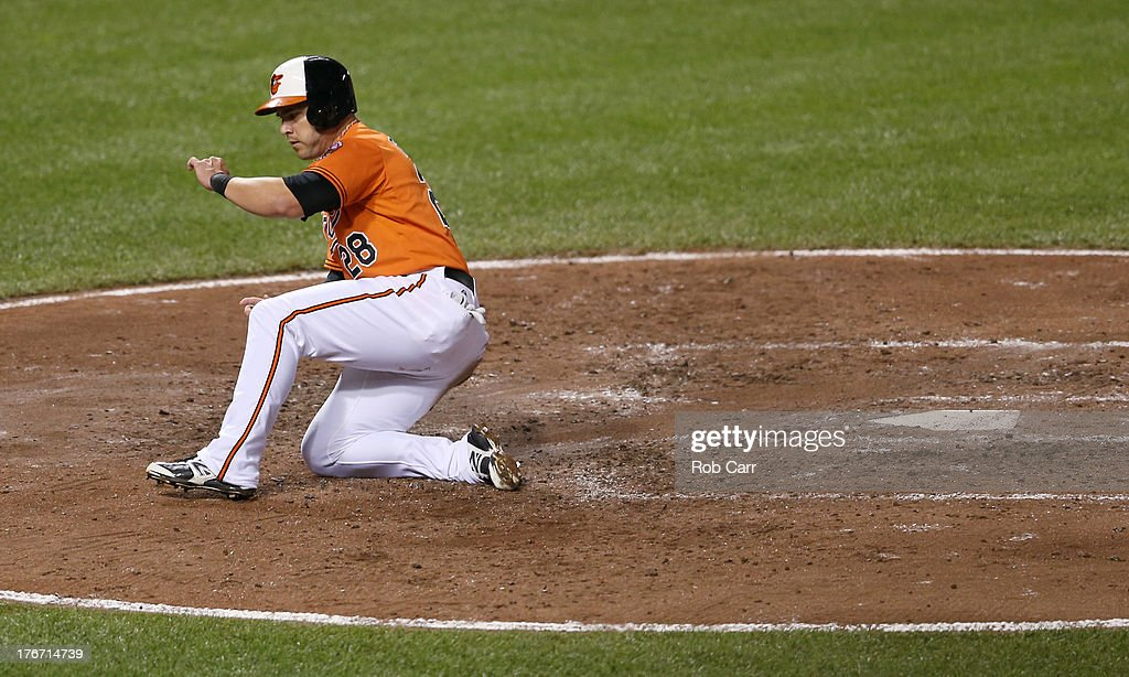 Steve Pearce #28 of the Baltimore Orioles scores a run against the Colorado Rockies during the third inning at Oriole Park at Camden Yards on August 17, 2013 in Baltimore, Maryland.