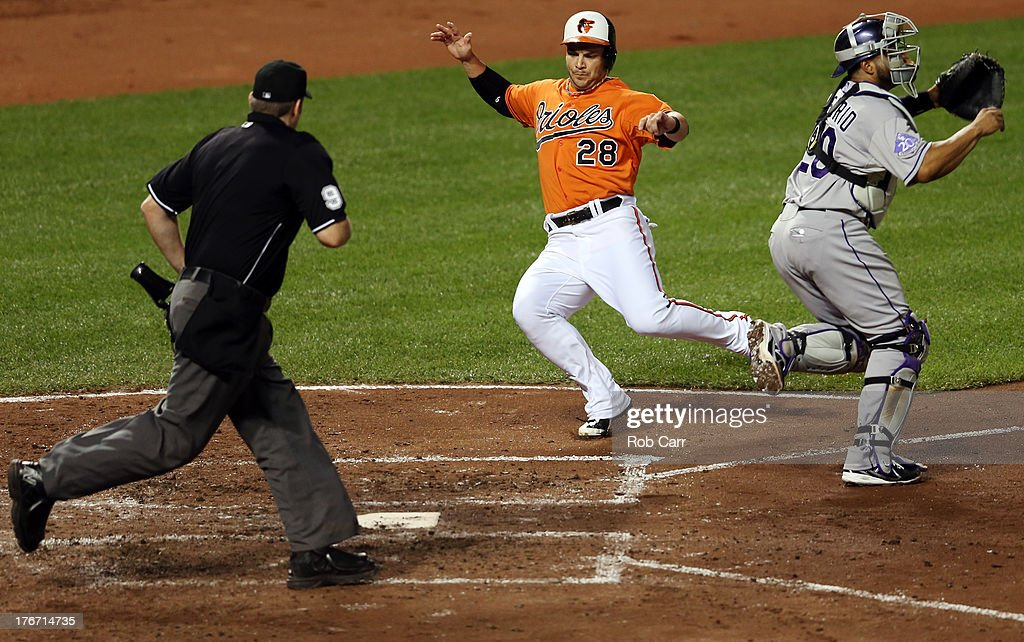 Steve Pearce #28 of the Baltimore Orioles scores a run in front of catcher <a gi-track='captionPersonalityLinkClicked' href=/galleries/search?phrase=Wilin+Rosario&family=editorial&specificpeople=5734314 ng-click='$event.stopPropagation()'>Wilin Rosario</a> #20 of the Colorado Rockies and home plate umpire Chris Conroy during the third inning at Oriole Park at Camden Yards on August 17, 2013 in Baltimore, Maryland.